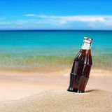 Sweating bottle of cola on the sand Royalty Free Stock Photography