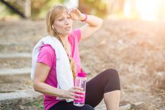 Sweating Fit Woman Outdoors With Towel and Water Bottle in Wo Royalty Free Stock Photography