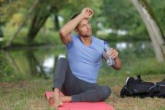 Sweating man having drink after exercising. Sweating man having a drink after exercising Stock Images