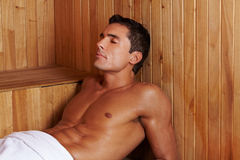 Sweating man in sauna. Sweating attractive man laying in a sauna Royalty Free Stock Photography