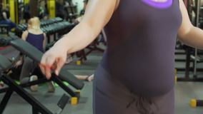 Sweating overweight girl skipping jump rope in sports club, fitness, slow-mo