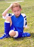 Sweaty. Young boy sitting on grassy soccer field resting at halftime Royalty Free Stock Image