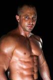 Sweaty bodybuilder. Sweaty strong man on the black background stock image