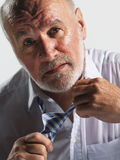 Sweaty Businessman Loosening Tie. Closeup of a sweaty middle aged businessman loosening tie against white background stock photo