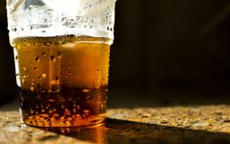 SWEATY CUP OF SODA ON COUNTERTOP. A partially empty cup of soda pop sits on a counter top with sweat dripping on the sides and bubbles inside royalty free stock images