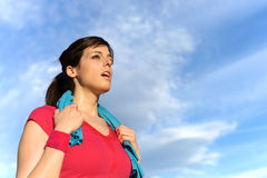 Tired fitness woman sweating after exercising. Sweaty fitness woman tired after training. Caucasian female athlete sweating and exhausted after exercising on sky Stock Images