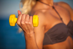 Sweaty fitness woman working out with dumbbells in summer on bea Royalty Free Stock Photography