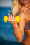 Sweaty fitness woman working out with dumbbells in summer on bea Stock Images