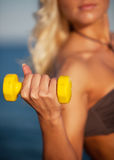 Sweaty fitness woman working out with dumbbells in summer on bea Royalty Free Stock Photo