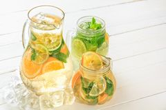 Sweaty glass jug in the ice and glasses with fresh lemonade stand on white wooden rustic boards in bright light. Stock Photography