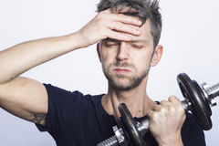 Sweaty gym session. Man looking tired holding a dumbbell Stock Photos