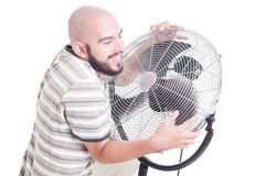 Sweaty and heated man hugging blowing fan or cooler Royalty Free Stock Photos