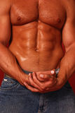 Sweaty male bodybuilder with hairy chest. Male bodybuilder cupping his hands with a hairy chest and 6 pack abdomen Stock Images