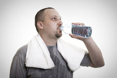 Sweaty man drinking water after exercise Stock Photo