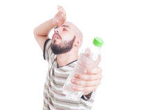 Sweaty man holding a bottle of cold water Stock Images