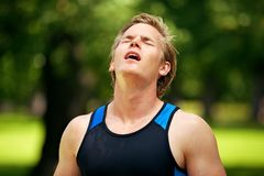 Sweaty Man Looking Exhausted. Sweaty young athlete looking up after a tiring workout Stock Photo