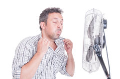 Sweaty man opening shirt in front of cooling fan. As refreshing in hot summer concept royalty free stock images