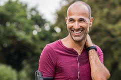Sweaty man resting after exercise. Mature man listening to music while resting after jogging. Happy bald senior man feeling refreshed after exercise. Portrait of Royalty Free Stock Photos