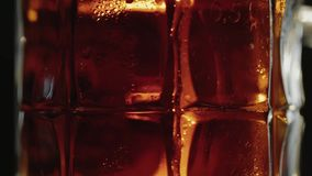 Sweaty mug of cold dark kraft beer, drops flow down the glass, in bar or pub. Close up panorama shot. Isolated black background. Slow motion stock footage
