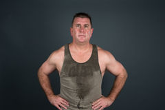 Sweaty muscular man after workout. A muscular man poses after a hot, sweaty workout and exercise regime stock image