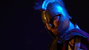 The sweaty Roman gladiator in leather armor, helmet and red raincoat stands with a pensive look and then turns to the. The sweaty Roman gladiator in armor and stock video footage