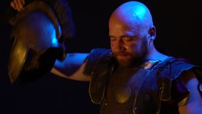 A sweaty Roman gladiator with sword in leather armor with a beard and bald head takes off his helmet and looks into the stock footage