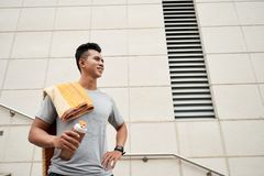 Sweaty runner. Sweaty smiling young jogger with towel and water bottle royalty free stock photos