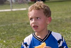Sweaty Soccer Player. Sweaty red faced soccer player eating orange at halftime Stock Images