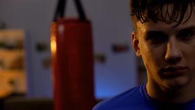 Sweaty teenager looks seriously after intensive boxing workout, facing challenge stock photo