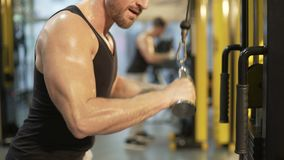 Sweaty upper body of guy doing pull-downs in gym, looking at his biceps. Stock footage stock video footage