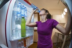 Sweaty woman drinking water seen from inside the fridge Royalty Free Stock Images