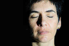 Sweaty women with eyes closed. Closed portrait of a woman with drops isolated on black Stock Images