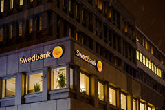 Swedbank商标在大厦门面的多雪的夜 免版税库存照片