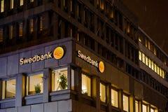 Swedbank-Logo auf einer schneebedeckten Nacht auf der Gebäudefassade Lizenzfreie Stockfotos