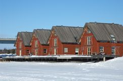 Sweden. Red houses along the frozen river in Umea north of Sweden royalty free stock images