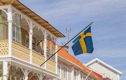 Sweden flag Marstrand. Swedish flag flying on a street with traditional wooden houses Marstrand, Sweden royalty free stock photo