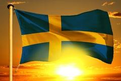 Sweden flag weaving on the beautiful orange sunset with clouds background. Sweden flag weaving on the beautiful orange sunset background royalty free stock photo