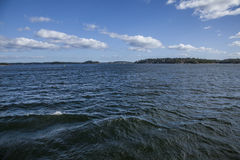 Sweden; the islands/dark waters. A view of some of the islands outside of the city of Stockholm, Sweden. The image was taken on a sunny day in March 2017; there Royalty Free Stock Photo