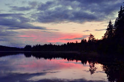 Sweden lake in sunset. Sunset in Sweden landscape with forest reflecting in lake Stock Photos