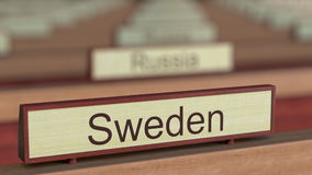 Sweden name sign among different countries plaques at international organization. 3D rendering Royalty Free Stock Image