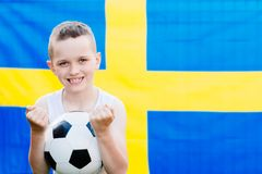 Sweden national football team supporter. Child boy with football ball and Sweden flag royalty free stock photography
