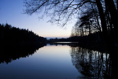 Sweden. Small lake at dusk with trees reflection Stock Photos