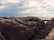 Two undefined people walking on a rock by the sea in Sweden. Swedish summer, walking outdoors, bright Stock Photography