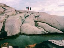 Three undefined people on a rock in Sweden. Trip to Sweden, sea in the front, clouds on the Stock Photos