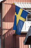 Sweden waving flag. On a red cottage Royalty Free Stock Images