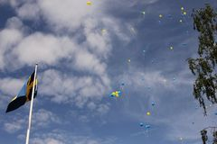 Swedens National Day. Celebration of Swedens National Day with the swedish flag and blue and yellow balloons flying in the sky stock photo