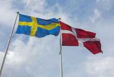 Swediah and Danish flag side by side. Blue sky. Royalty Free Stock Photo