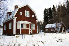 Swedish Architecture. Two red wooden traditional swedish homes in a winter landscape Stock Photo