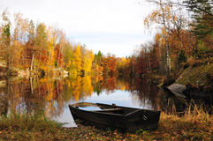 Swedish autumn. October's lake view with old boat Royalty Free Stock Photo
