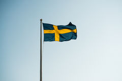 Swedish banner. Swedish flag towards a clear blue sky stock images